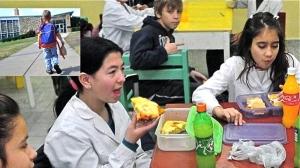 Los colegiales en el comedor del colegio comiendo su propia comida