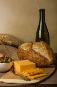 17453224-un-bodegon-con-queso-salchicha-aceitunas-botella-de-vino-y-pan-en-una-tabla-de-cortar